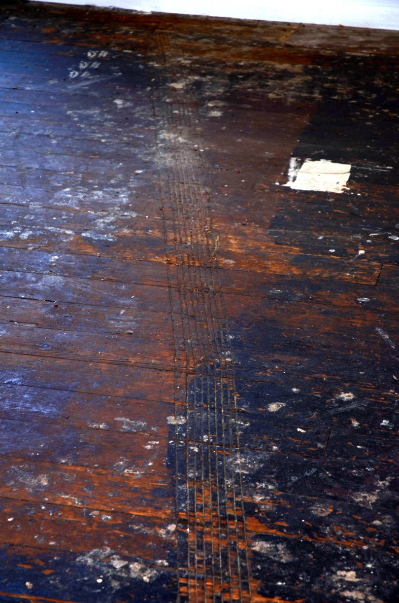 Tires marks etched from a motorcycle on the wood floor of the house .